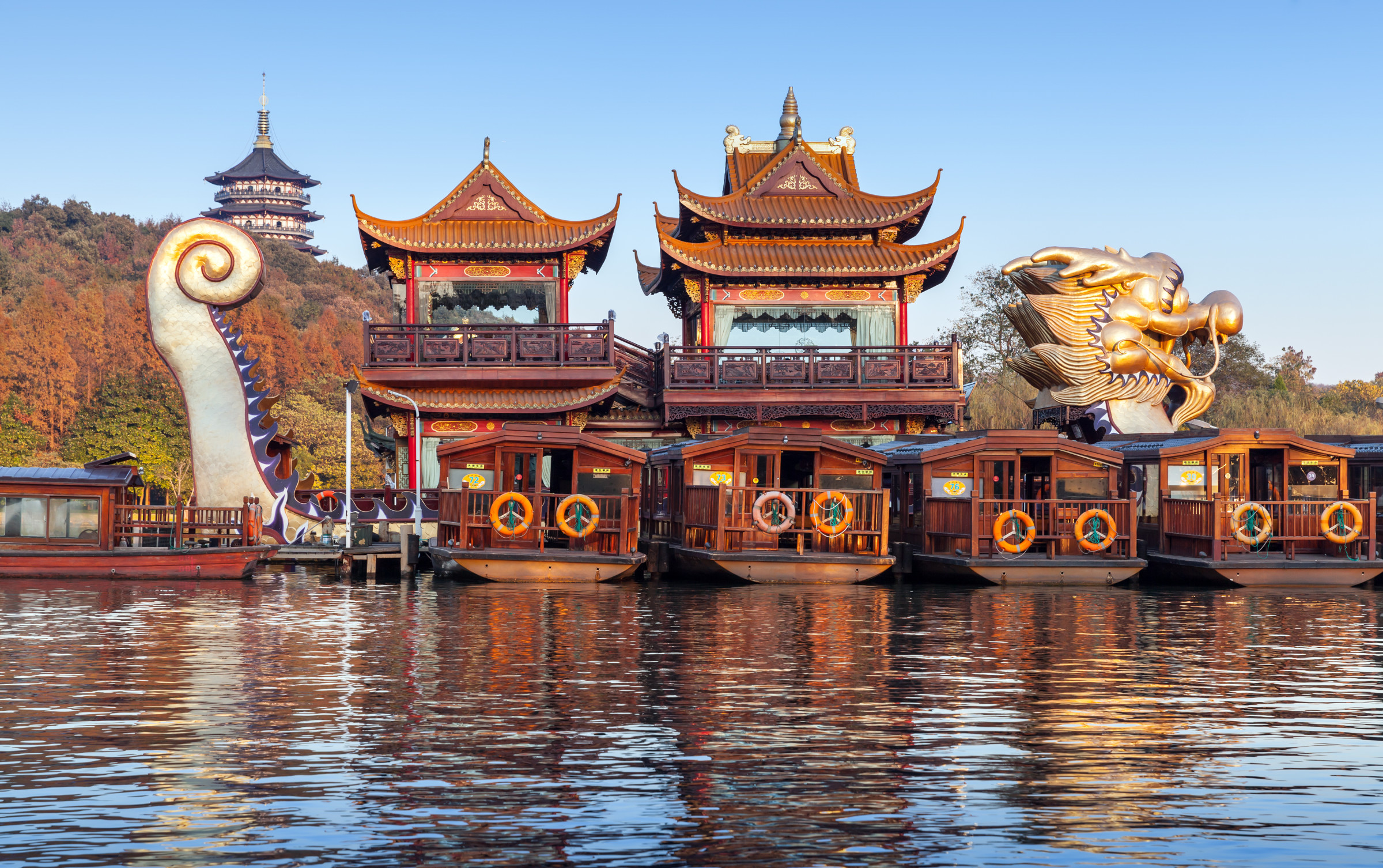 Hangzhou China - December 5 2014: Traditional Chinese wooden recreation boats and Dragon ship are moored on the West Lake. Famous park in Hangzhou city center China